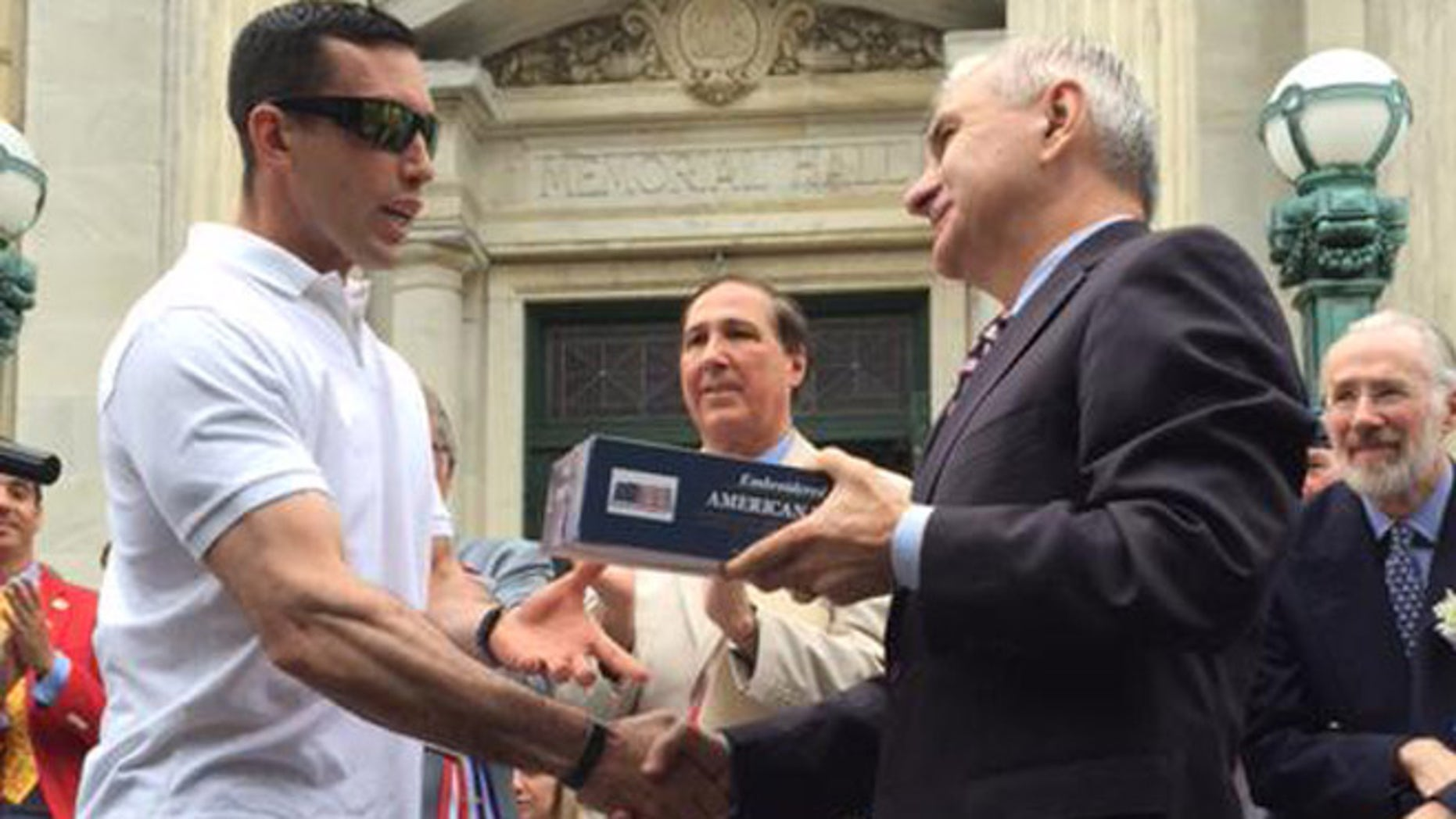 Green Beret P. Andrew McKenna, left, receives a flag that flew over the U.S. Capitol from Sen. Jack Reed (D-R.I.) at Bristol, R.I., Fourth of July parade. (Photo courtesy of Reed) .