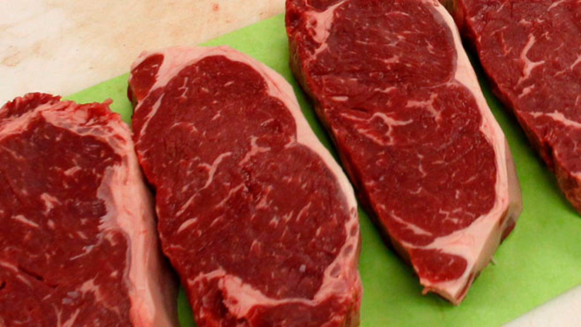 April 25, 2012: Strip steaks sit on the butchers table.