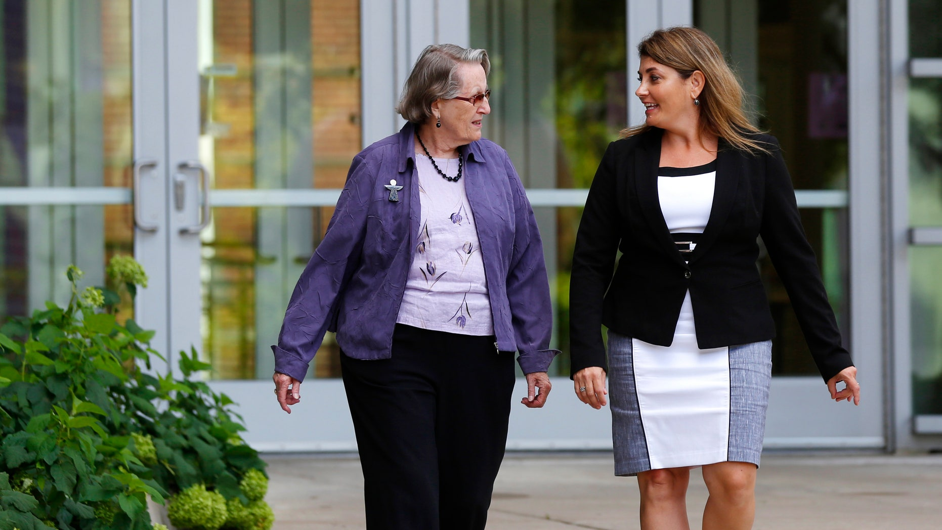 In this Aug. 11, 2016 photo, Angela McArthur, right, director of the Anatomy Bequest Program at the University of Minnesota Medical School, walks with Jean Larson, widow of a donor in Minneapolis. Once a relatively rare option, body donation has surged at medical schools, including the University of Minnesota. The increase has helped provide cadavers for dissection by first-year medical students, and for research and surgical training.