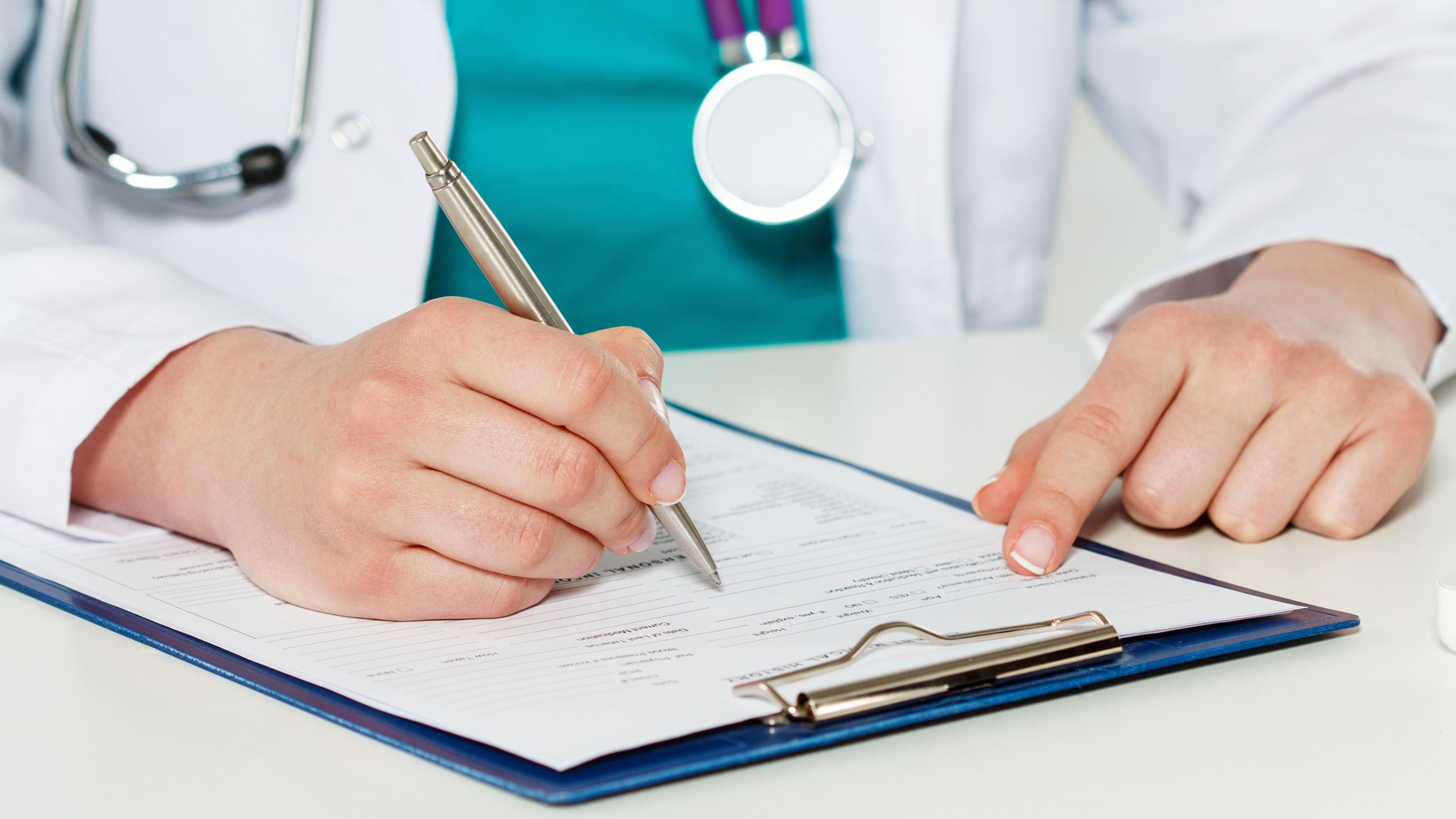 Female medicine doctors hands filling patient medical form. Physician working with paper in hospital office room. Therapeutist sitting at working table making some paperwork. Hands holding silver pen