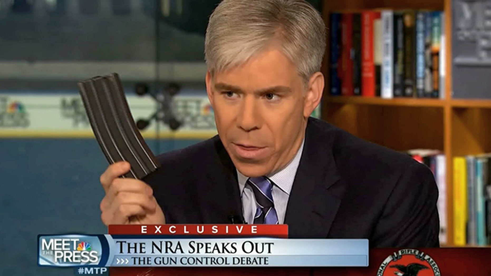 """This video frame grab image provided by""""Meet the Press"""" shows host David Gregory holding what he described as a high-capacity ammunition magazine during a recent Sunday's program."""