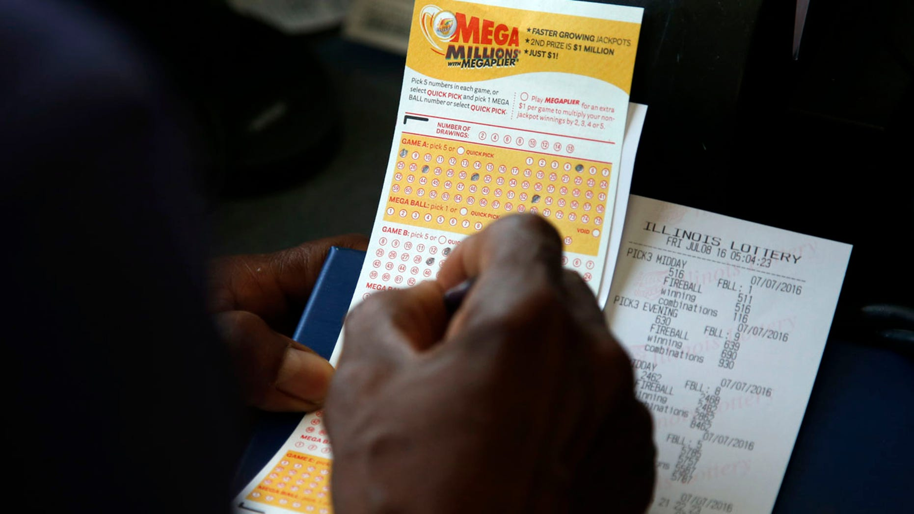 July 8, 2016: A customer picks numbers for his Mega Millions lottery ticket at a convenience store in Chicago.