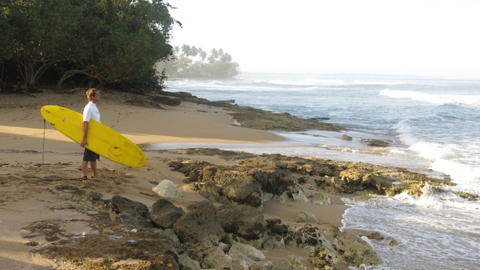 A surfer studies the waves at Wilderness Beach in Aguadilla, Puerto Rico.