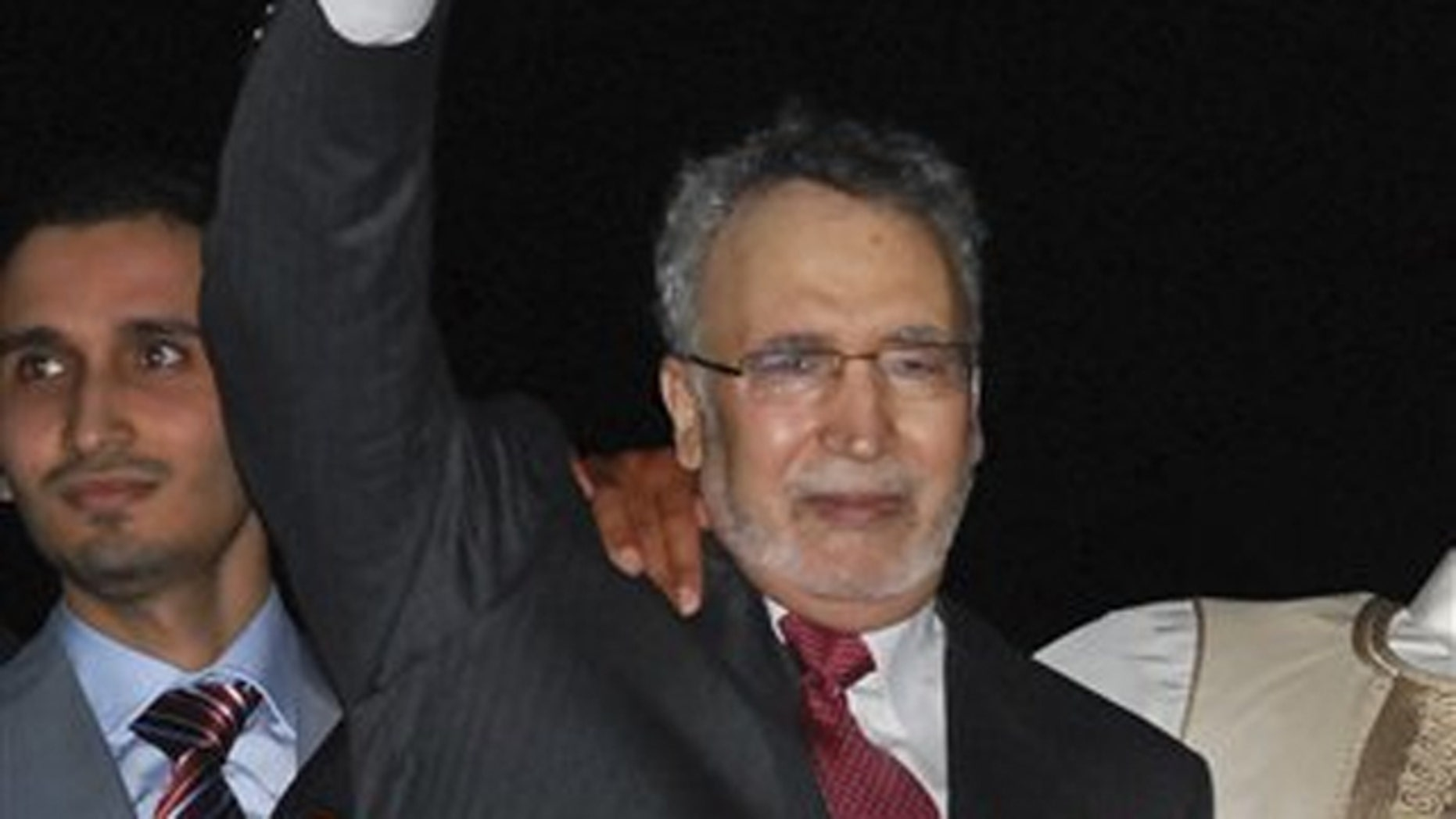 In this Aug. 20, 2009, file photo, Abdelbaset al-Megrahi gestures on his arrival at an airport in Tripoli, Libya.