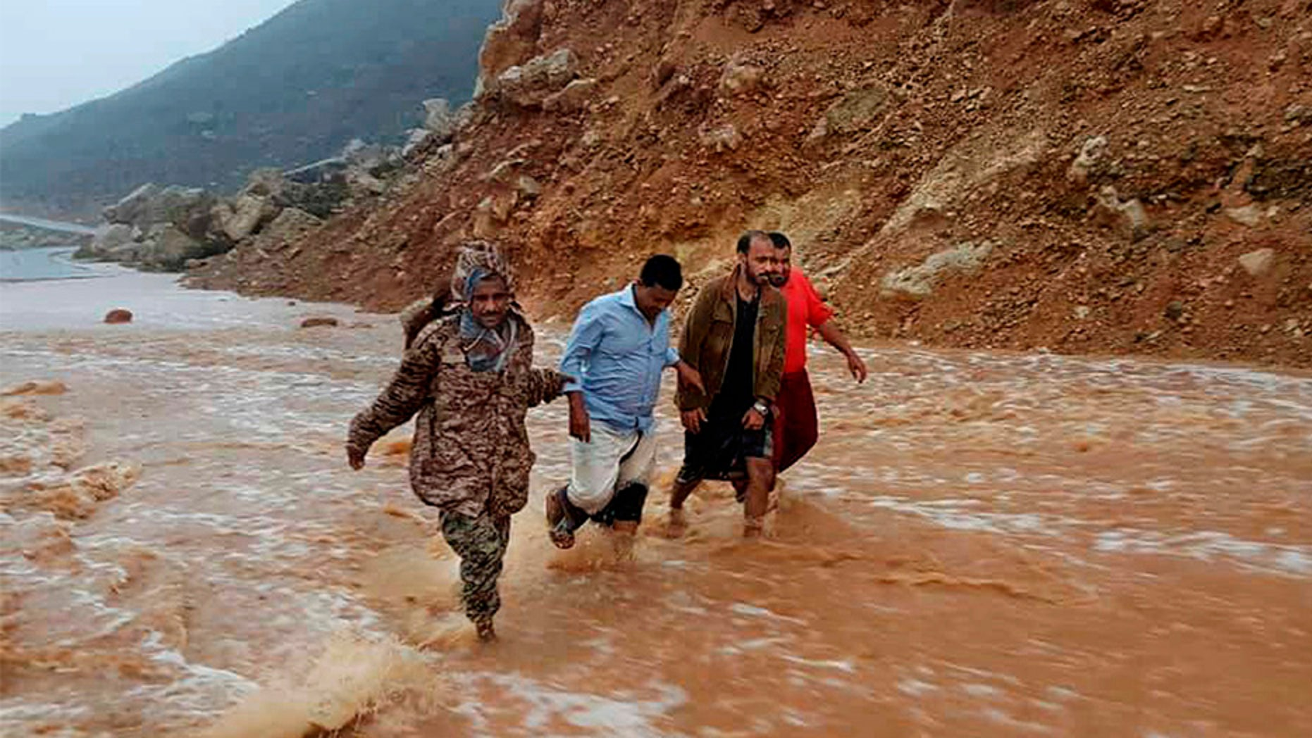 May 24, 2018: Men walk on a road flooded after heavy rain and strong winds caused damage in Hadibu as Cyclone Mekunu pounded the Yemeni island of Socotra.