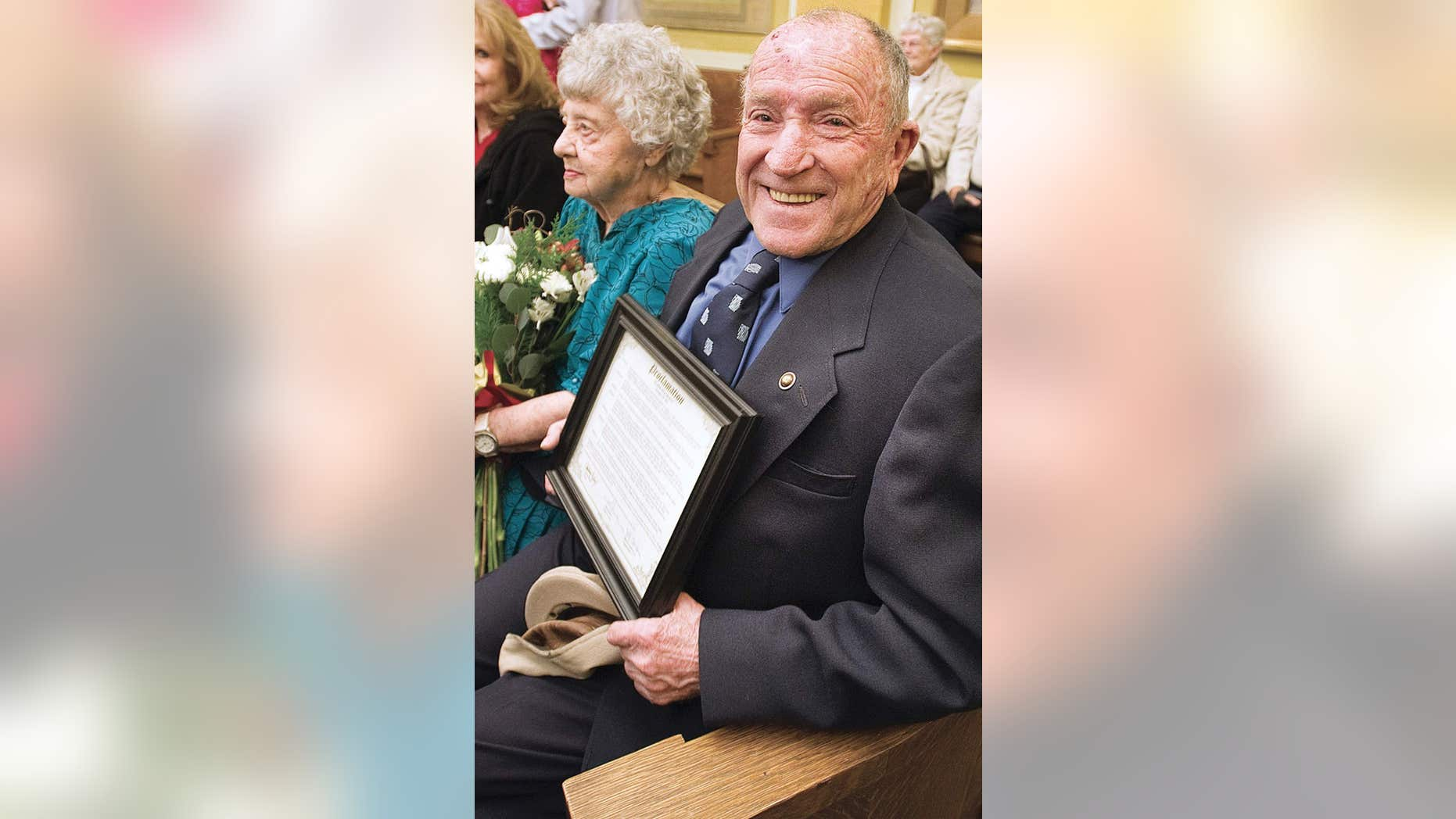 """In this 2012 photo, Elmer Melchi smiles as he sits with his wife, June, after commissioners proclaimed it """"Elmer Melchi Day."""""""