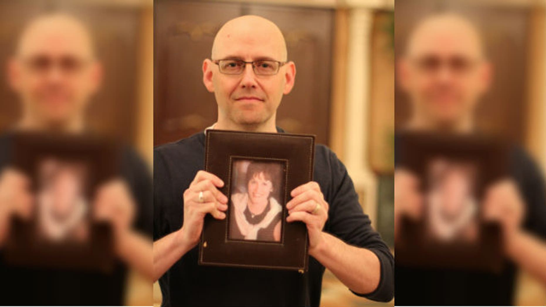 Best-selling author Brad Meltzer holding a photo of his high school teacher, Ellen Sherman. Meltzer used social media to find a kidney donor for Sherman. (Credit: Ryan Kuttler)