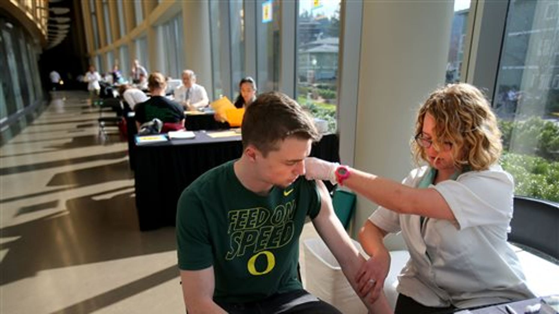FILE - In this Monday, March 2, 2015 photo, pharmacist Jenna Wright administers the Meningitis B vaccine to University of Oregon freshman Drew Russert during a mass vaccination clinic at Matthew Knight Arena in Eugene, Ore. after an outbreak of meningococcemia, resulting in the death of a student. (AP Photo/The Register-Guard, Brian Davies)