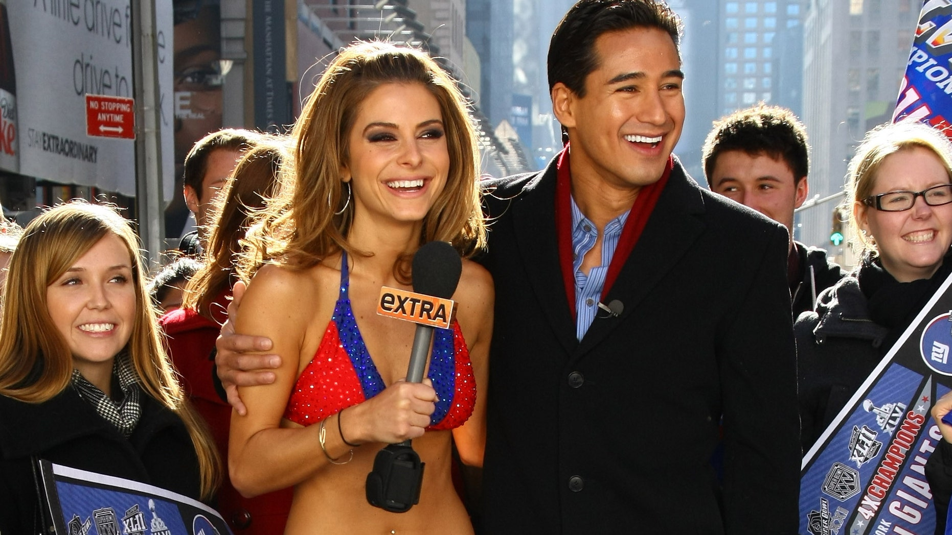 "NEW YORK, NY - FEBRUARY 06:  ""Extra"" hosts Mario Lopez (R) and Maria Menounos, an avid New England Patriots fan, makes good on her Super Bowl bet with her fellow show correspondent, Giants fan AJ Calloway and bares all in a New York Giants Bikini in Times Square on February 6, 2012 in New York City.  (Photo by Neilson Barnard/Getty Images)"