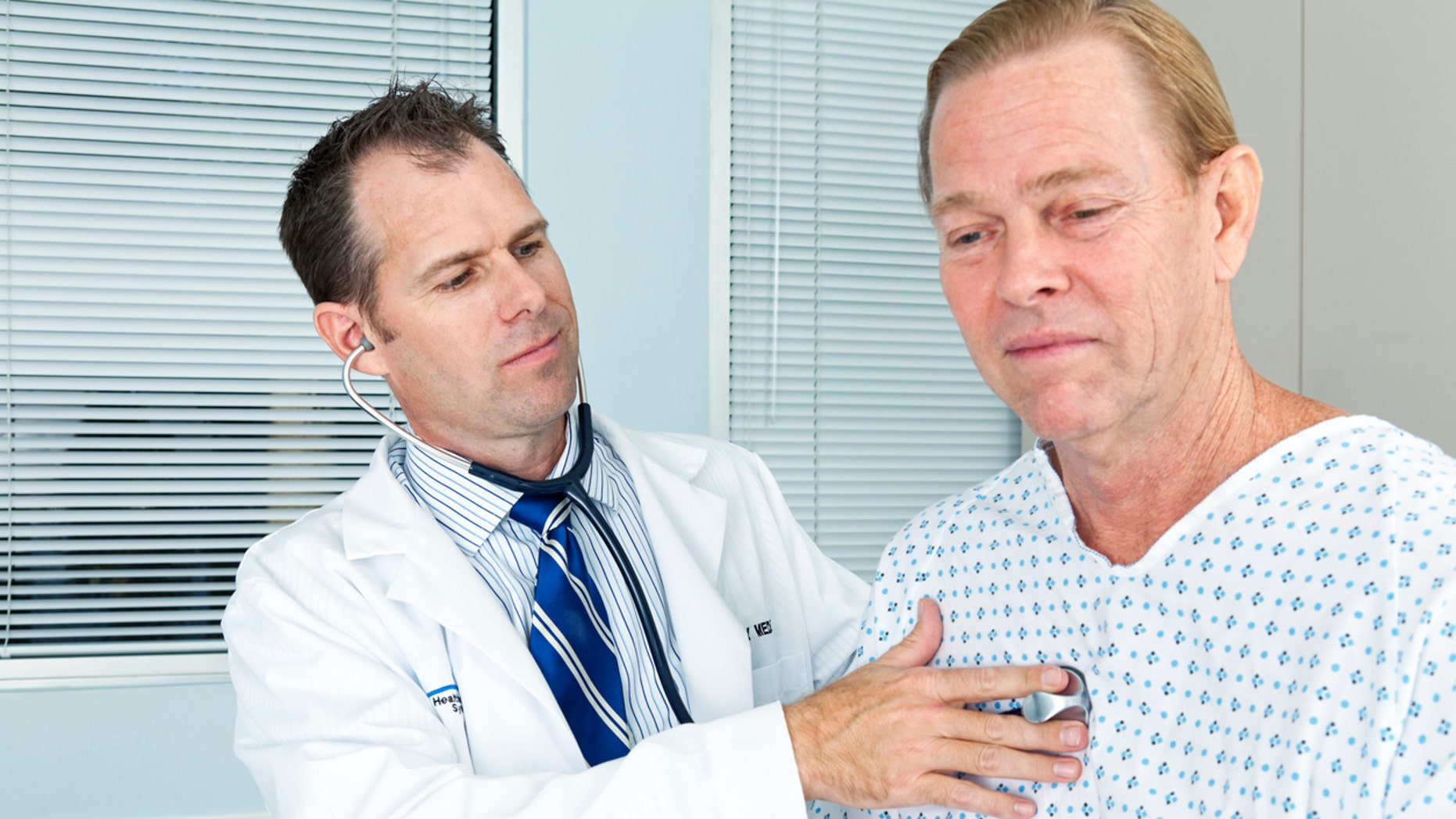 A doctor listens to a patients chest with a stethoscope.