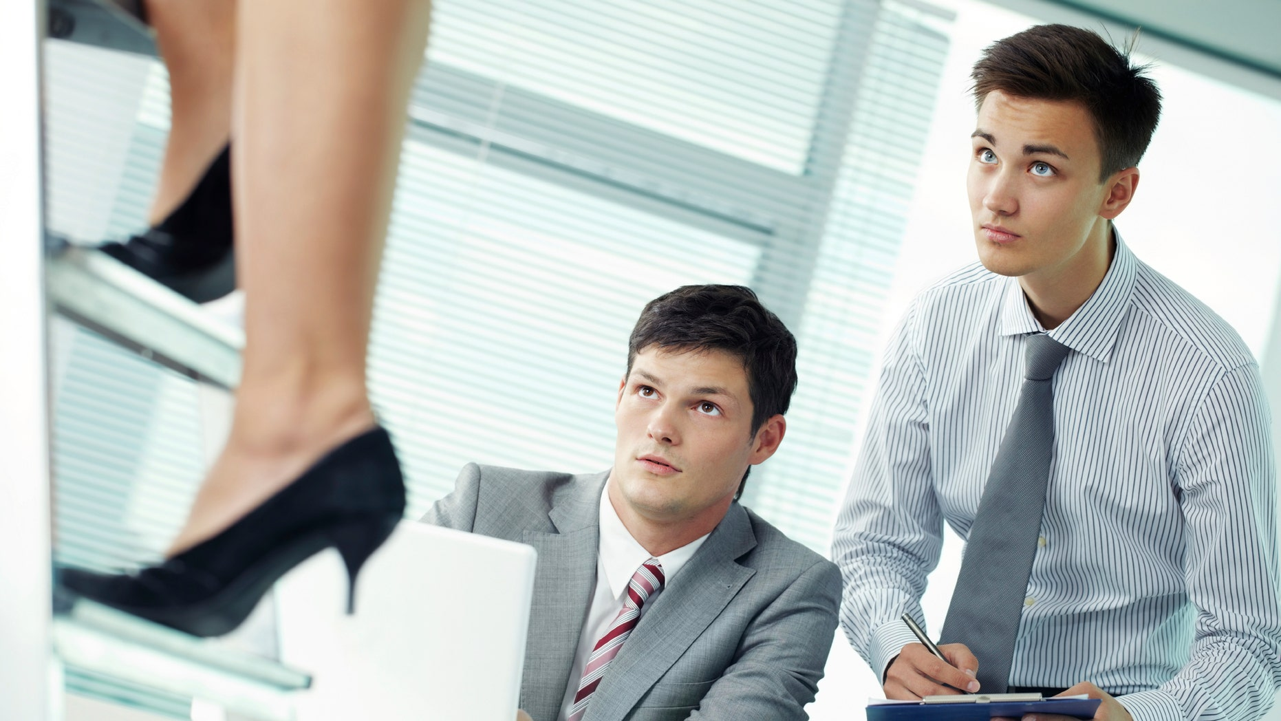 Two shocked managers looking at legs of their female colleague