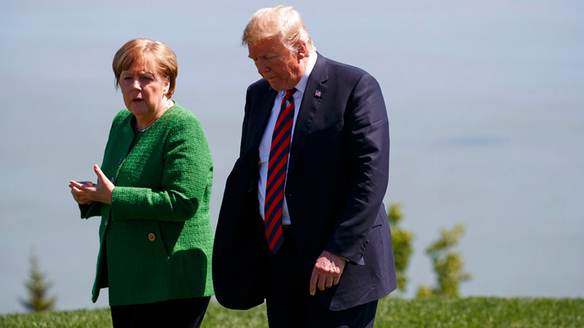 President Donald Trump, right, talks with German Chancellor Angela Merkel after the family photo during the G7 Summit, Friday, June 8, 2018, in Charlevoix, Canada. (AP Photo/Evan Vucci)