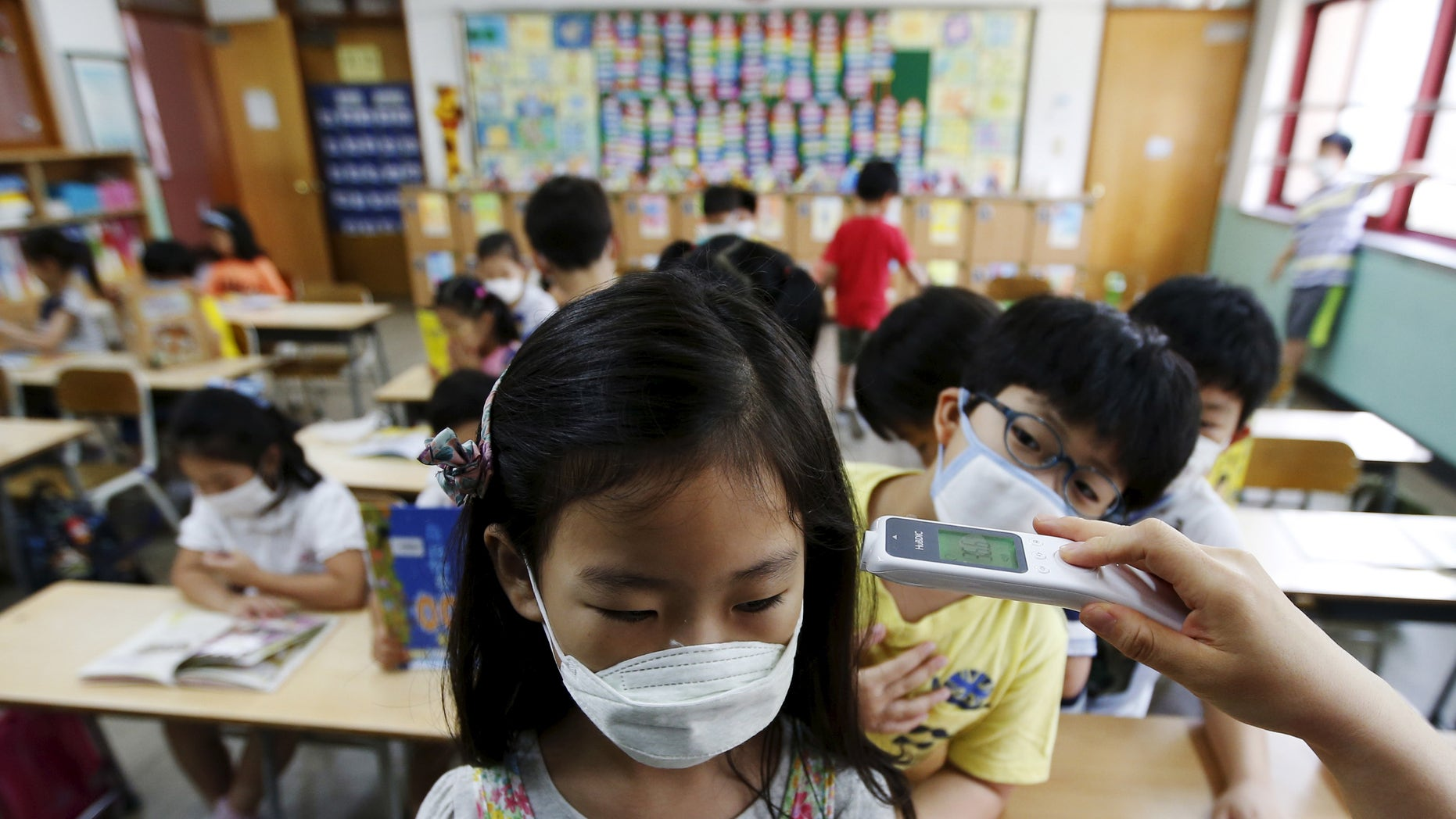 An elementary school student wearing a mask to prevent contracting Middle East Respiratory Syndrome (MERS), receives a temperature check at an elementary school in Seoul, South Korea, June 9, 2015. REUTERS/Kim Hong-Ji