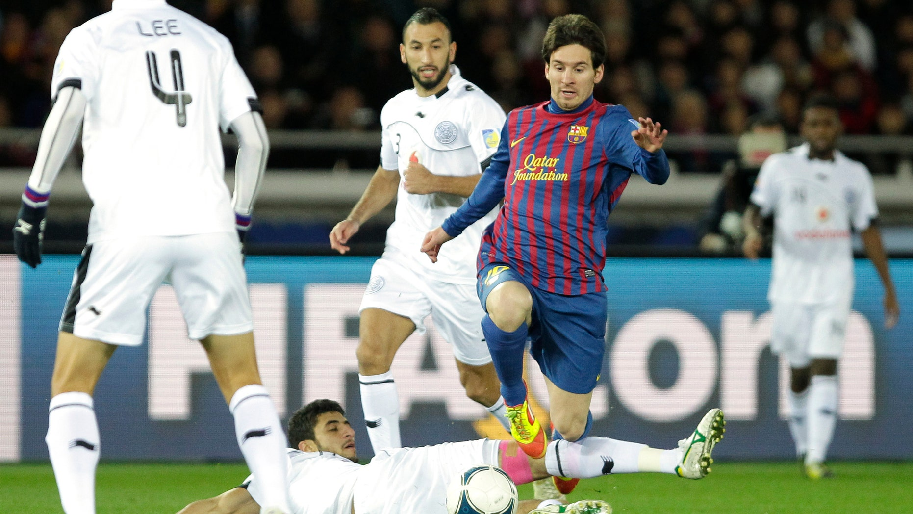 Spain's FC Barcelona midfielder Lionel Messi avoids a tackle by Qatar's Al-Sadd Sports Club defender Ibrahim Abdulmajed during their semifinal match of the Club World Cup soccer tournament in Yokohama, near Tokyo, Thursday, Dec. 15, 2011. (AP Photo/Shizuo Kambayashi)