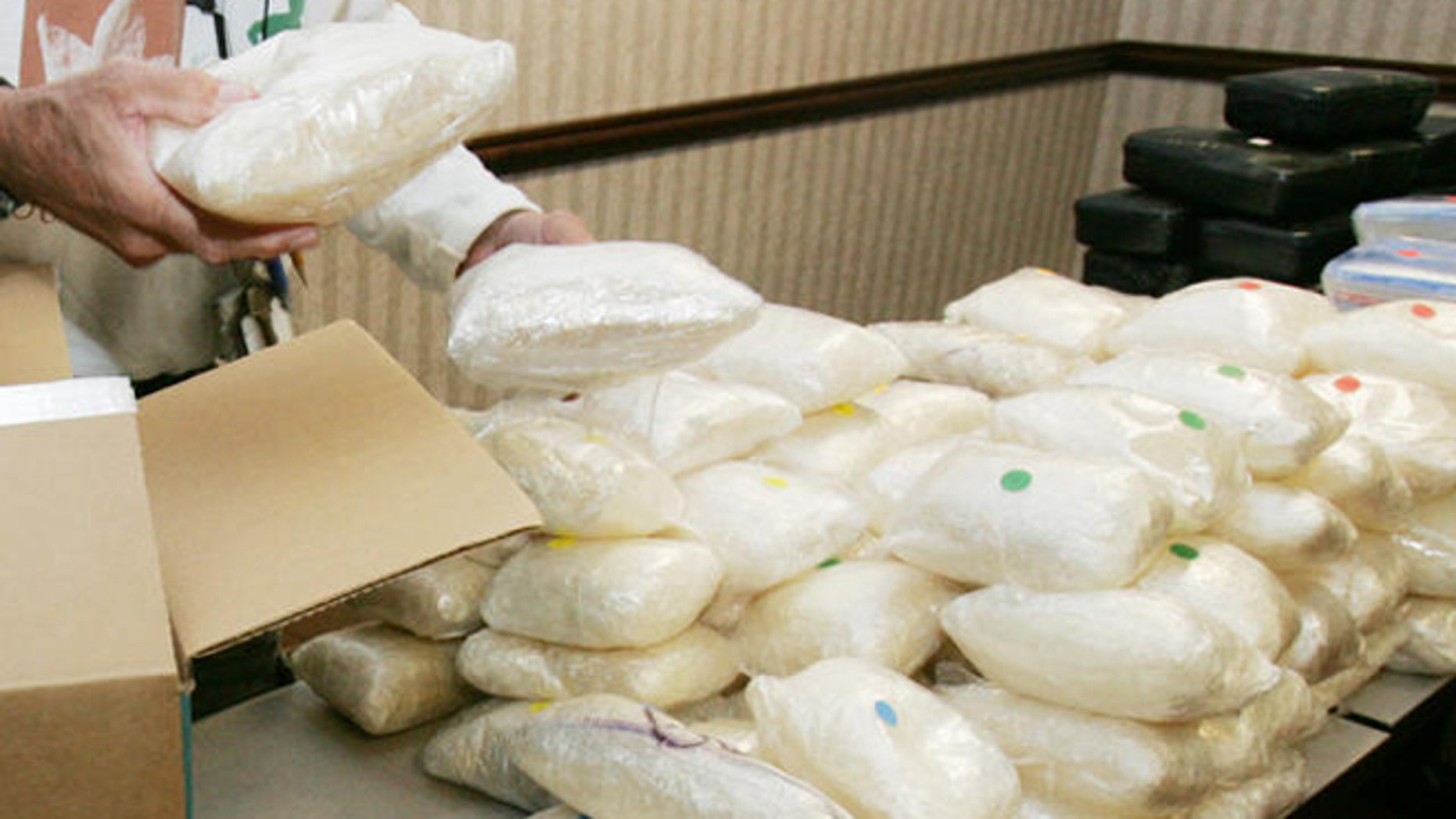 A U.S. Drug Enforcement Administration agent shows some of the 187 plus pounds of methamphetamine.