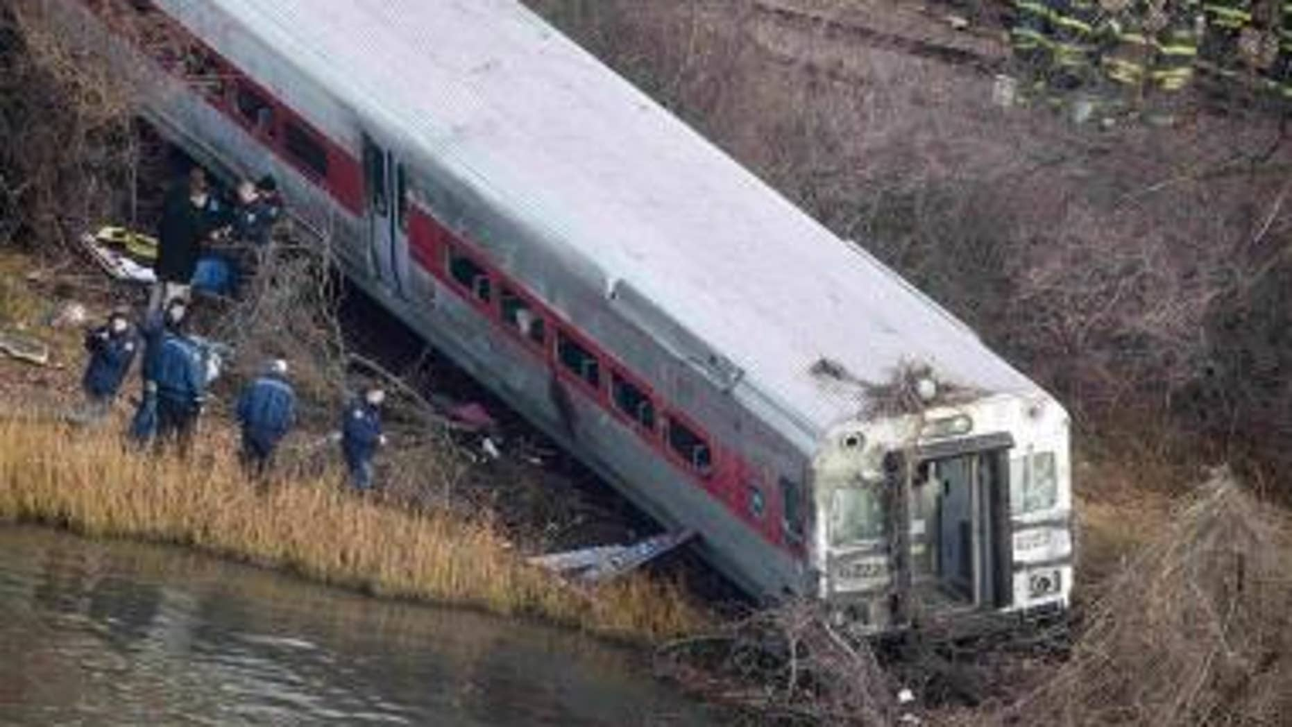 Emergency workers gather at the site of a Metro-North train derailment in the Bronx borough of New York, Dec. 1, 2013.