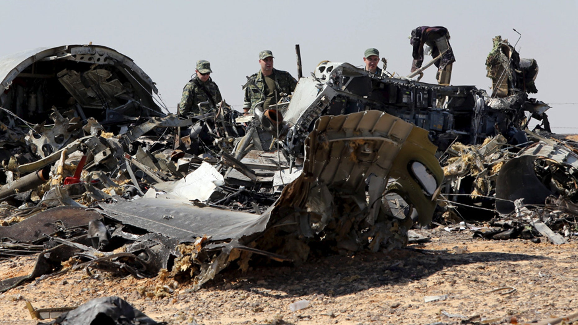 Nov. 1, 2015: Military investigators from Russia stand near the debris of a Russian airliner at the site of its crash at the Hassana area in Arish city, northern Egypt.