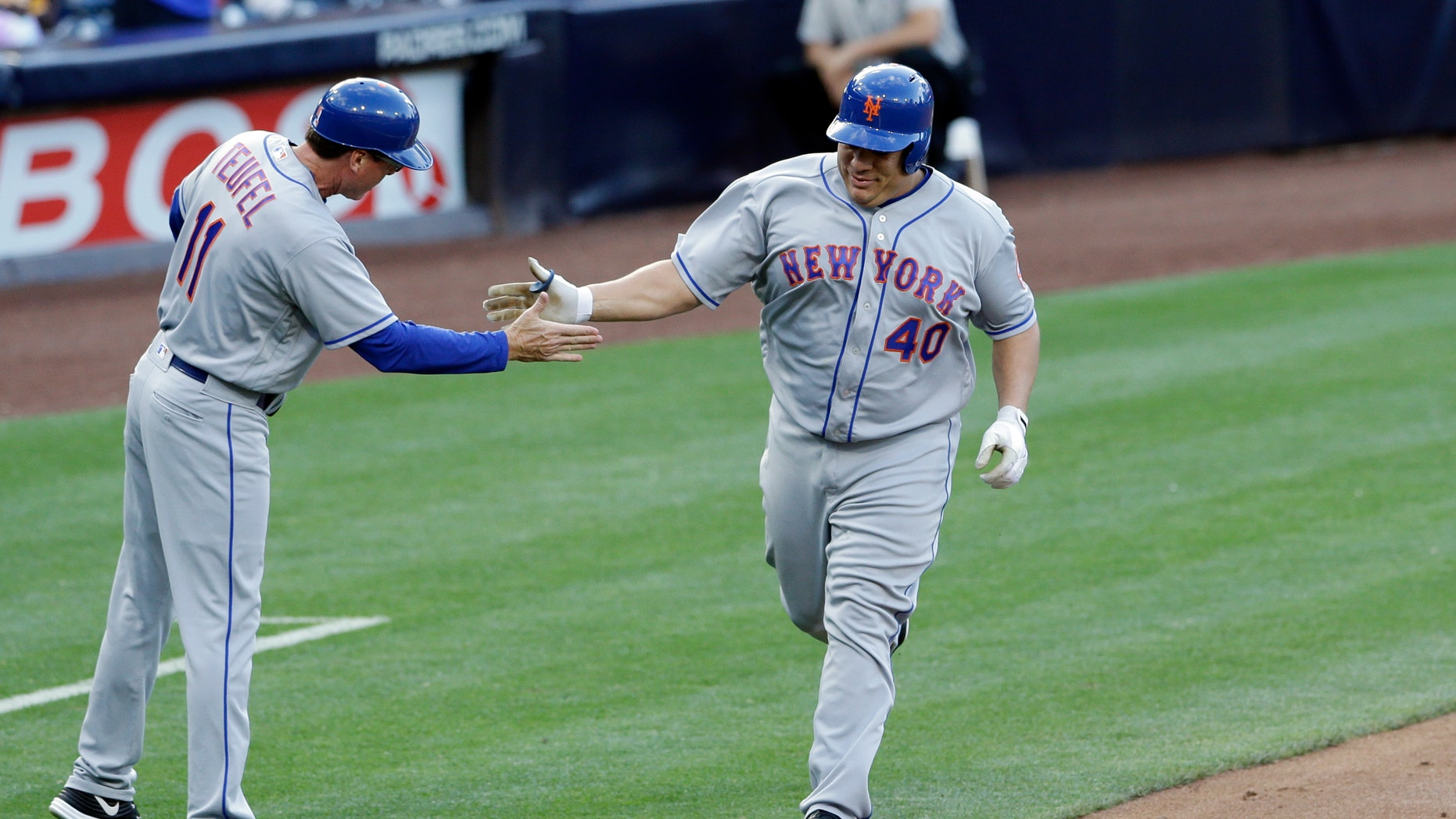 Bartolo Colon is greeted by third base coach Tim Teufel after hitting his first career home run.