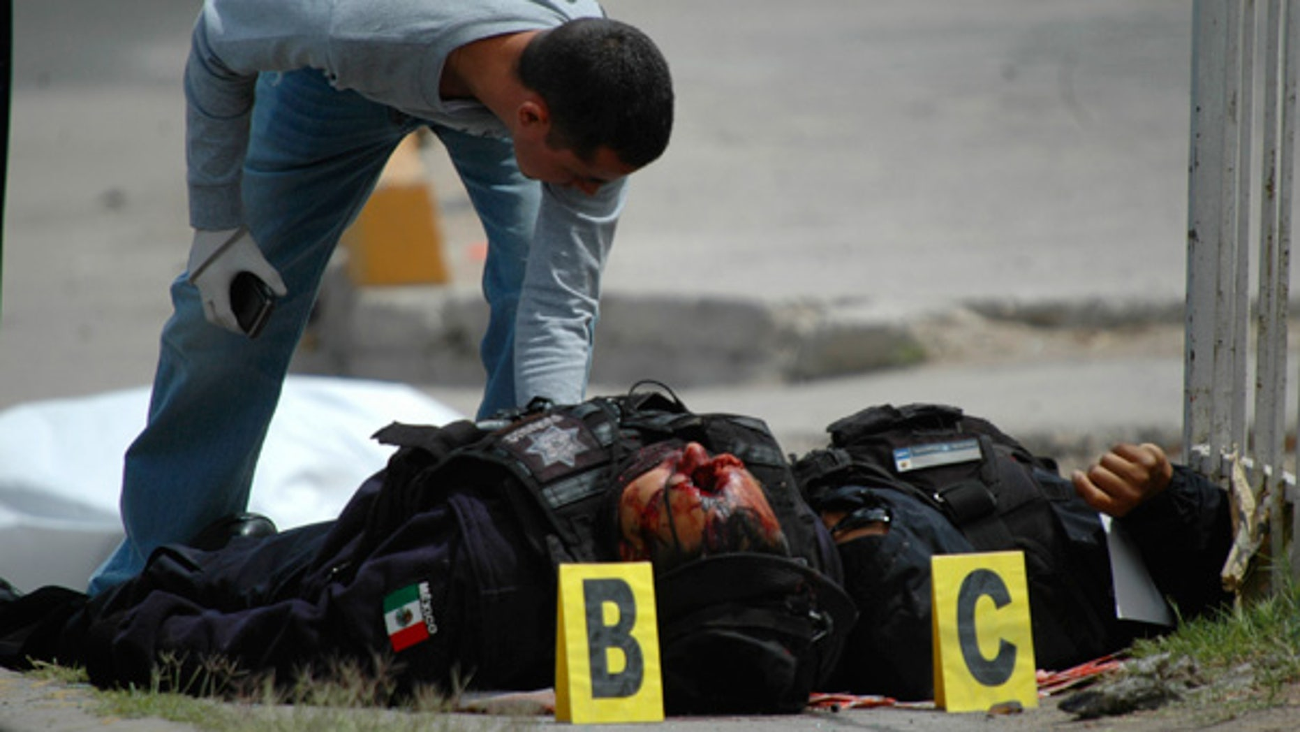 April 23: Police forensics expert examines the bodies of federal policemen that were killed after being ambushed in Ciudad Juarez.