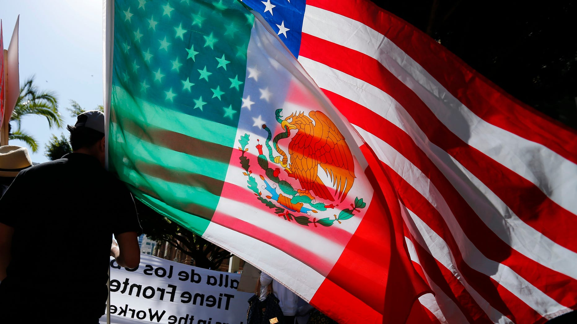 May 1, 2013: A youth carries national flags of the U.S. and Mexico through the streets of San Diego, during a demonstration about workers rights and immigration reform.