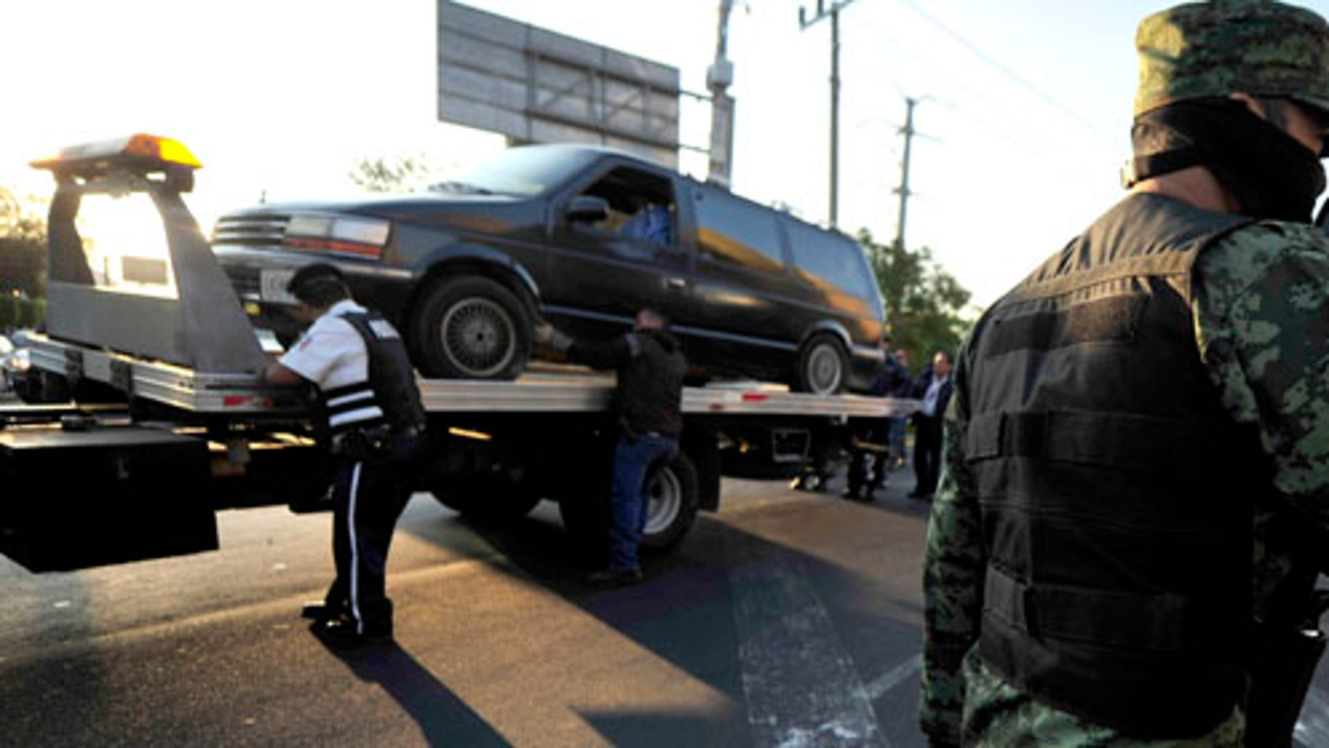 A soldier patrols as a vehicle that was discovered carrying bodies inside is taken away in Guadalajara, Mexico, Thursday Nov. 24, 2011.  At least 20 bodies were discovered early Thursday in three vehicles abandoned in the heart of Guadalajara, Mexico's second-largest city and the site of the recent Pan American Games, according to an official with the prosecutor's office in the state of Jalisco. (AP Photo/Victor Fernandez)