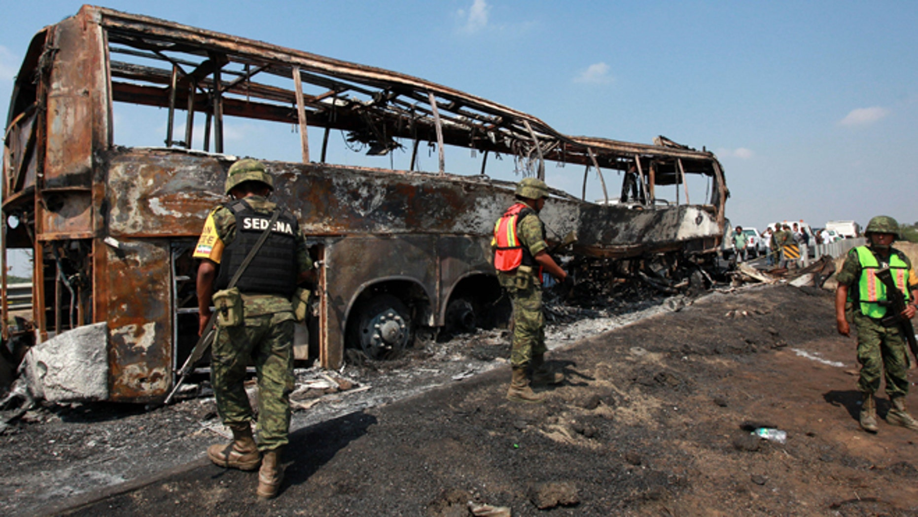 April 13, 2014: Soldiers guard the site where a passenger bus slammed into a broken-down truck and burst into flames near the town of Ciudad Isla in the Gulf state of Veracruz, Mexico. Dozens of people traveling on the bus to Mexico City burned to death inside the bus.