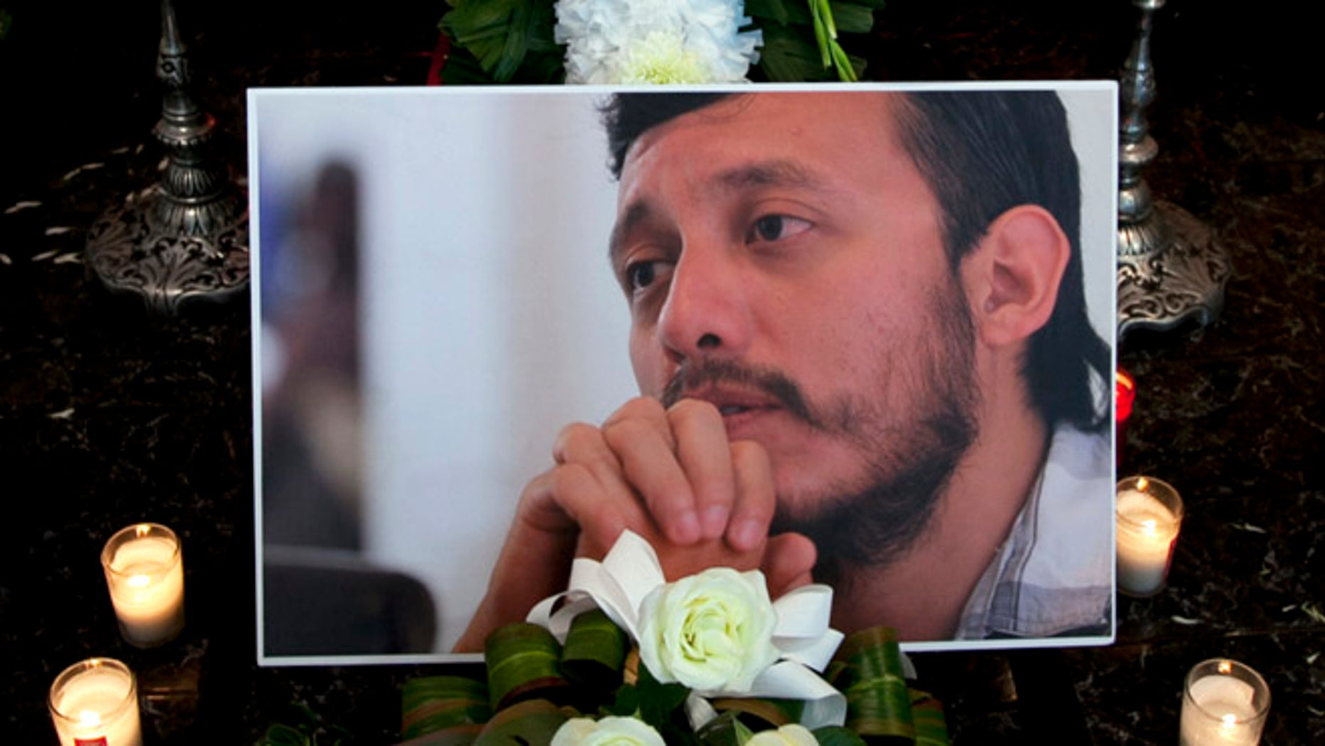 A photograph of murdered photojournalist Ruben Espinosa sits among flowers and candles in front of his casket inside a funeral home before his wake begins in Mexico City, Monday, Aug. 3, 2015.