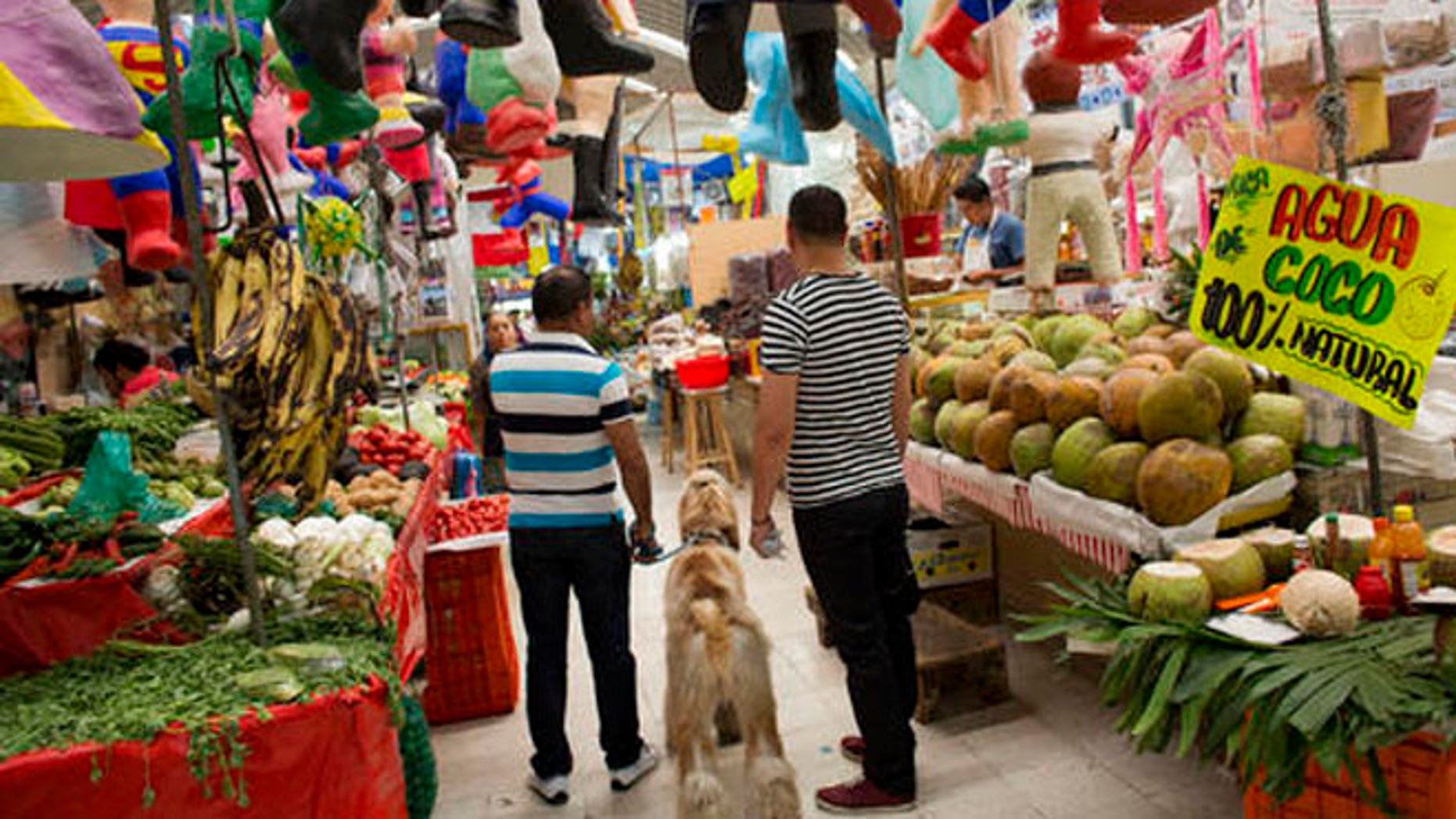 """Men shop along with their dog inside Mercado Medellin in Mexico City, Friday, May 20, 2016. Mexico is lowering its economic growth forecast for 2016, citing what it calls """"adverse"""" international conditions including sluggish industrial production in the United States. (AP Photo/Rebecca Blackwell)"""