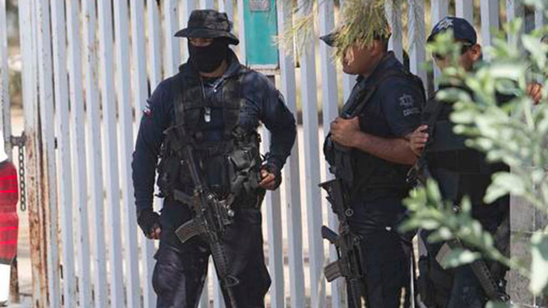 FILE - In this May 22, 2015, file photo, Mexican state police stand guard near the entrance of Rancho del Sol, where a shootout with the authorities and suspected criminals happened near Vista Hermosa, Mexico. Mexico's National Human Rights Commission said on Thursday, Aug. 18, 2016, that it has concluded that 22 people were arbitrarily executed by federal police during the event. Commission President Luis Raul Gonzalez Perez said their investigation revealed a range of human rights abuses on the part of government forces. (AP Photo/Refugio Ruiz, File)