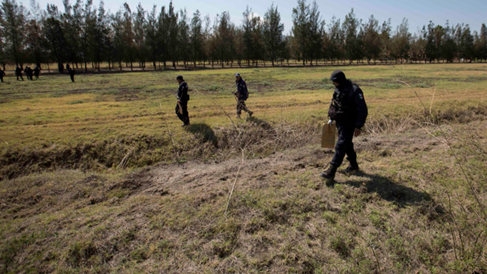Police comb a field for evidence in the Rancho del Sol, a ranch in the municipality of Ecuandureo, Mexico, Saturday, May 23, 2015. The latest in a series of clashes between Mexican authorities and a powerful, fast-growing drug cartel turned into the deadliest confrontation in recent memory, with 42 suspected gang gunmen and one Federal Police officer killed on Friday during a three-hour firefight at this remote western ranch. (AP Photo/Eduardo Verdugo)