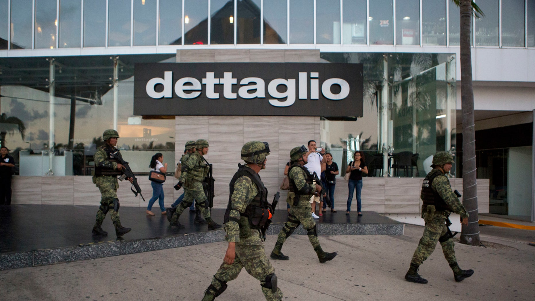 Soldiers walk outside Plaza Las Americas mall following reports of gunfire in Cancun, Mexico, Tuesday, Jan. 17, 2017.