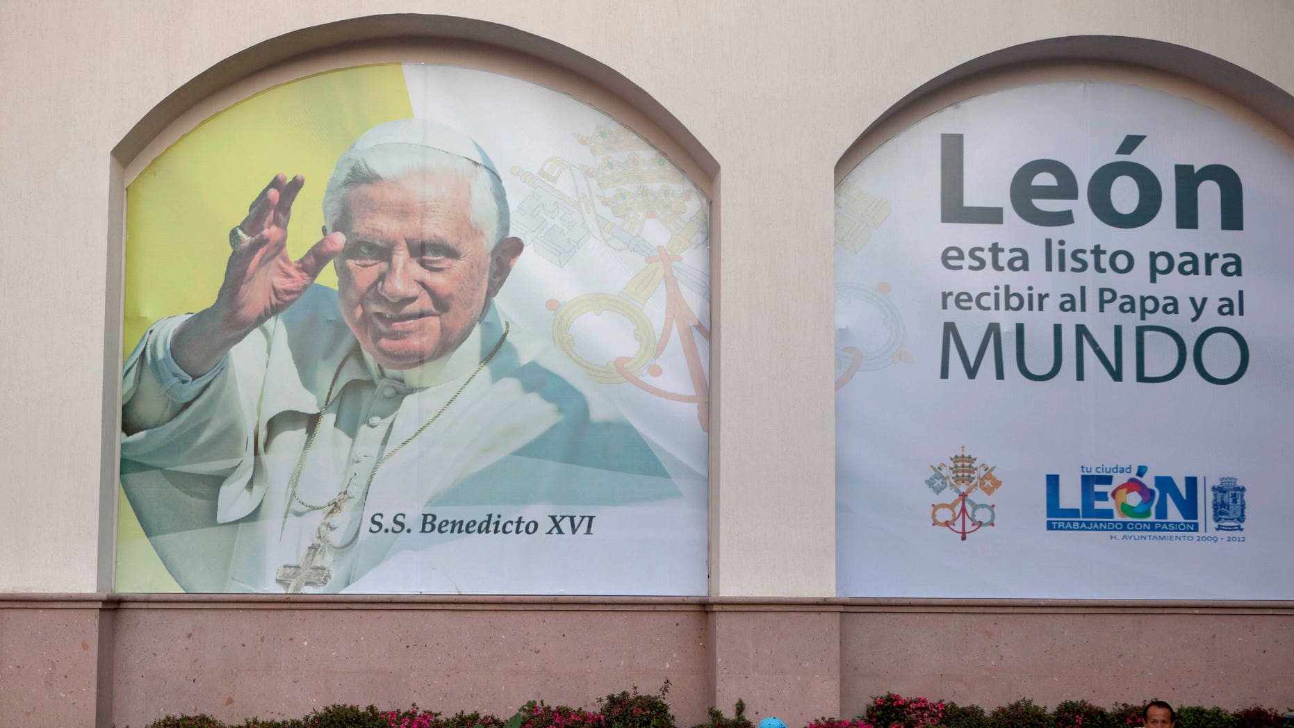 "People sit in front of a banner placed over a wall with an image of Pope Benedict XVI that reads in Spanish ""Leon is ready to receive the Pope and the world,"" in Leon, Mexico, Tuesday March 20, 2012. Benedict XVI will visit Mexico for the first time on March 23. (AP Photo/Eduardo Verdugo)"