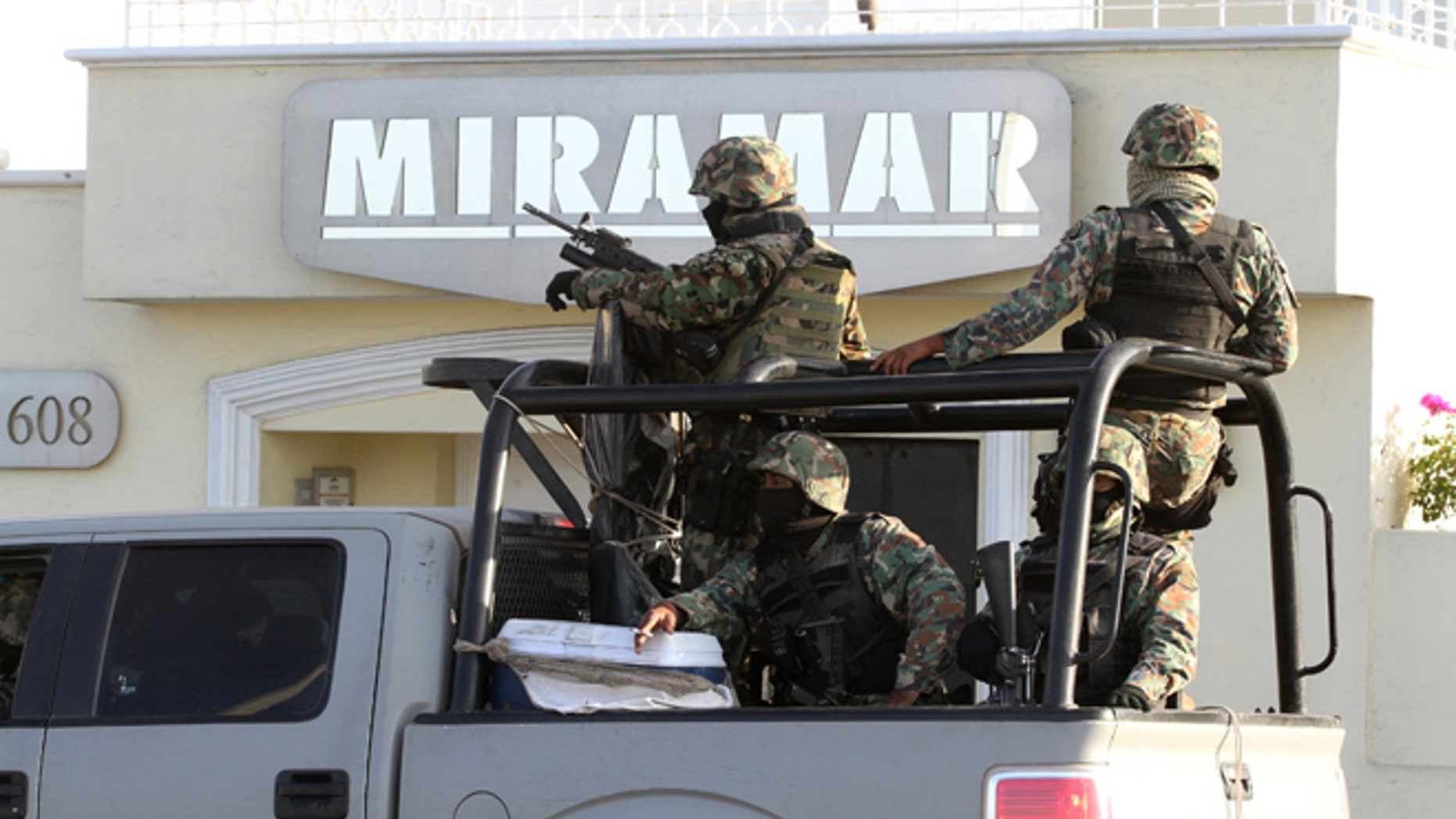Feb. 22, 2014: Military personnel stand atop a truck during a raid in Mazatlan, Mexico.