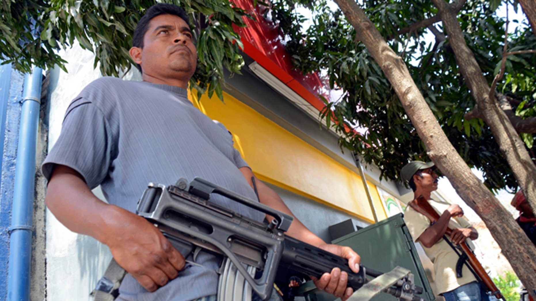 March 27, 2013: A group of armed vigilantes stand at the entrance to the town of Tierra Colorada, Mexico. Hundreds of armed vigilantes have taken control of this town on a major highway in the Pacific coast state of Guerrero, arresting local police officers and searching homes after a vigilante leader was killed. Several opened fire on a car of Mexican tourists headed to the beach for Easter week.