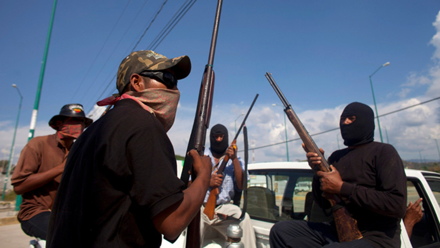 Jan. 18, 2013: In this photo, masked and armed men sit in the back of a pick-up truck at the entrance to the town of Ayutla, Mexico.  Hundreds of  men in the southern Mexico state of Guerrero have taken up arms to defend their villages against drug gangs, a vigilante movement born of frustration at extortion, killings and kidnappings in a region wracked by violence.