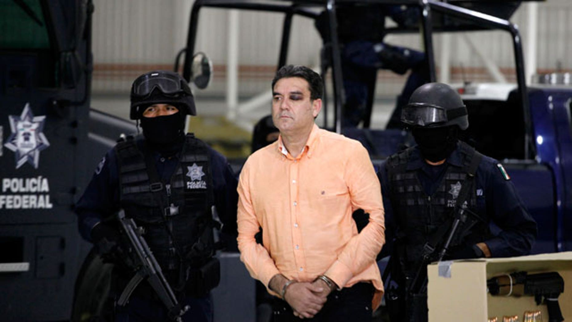 "Police officers escort suspected drug trafficker Manuel Fernandez as he is presented to the media at the federal police headquarters in Mexico City, Monday Nov. 8, 2010. According to federal police Fernandez, an alleged member of the criminal organization led by Joaquin Guzman Loera, aka ""El Chapo Guzman"", was arrested Sunday in the northern city of Culiacan, Sinaloa state."