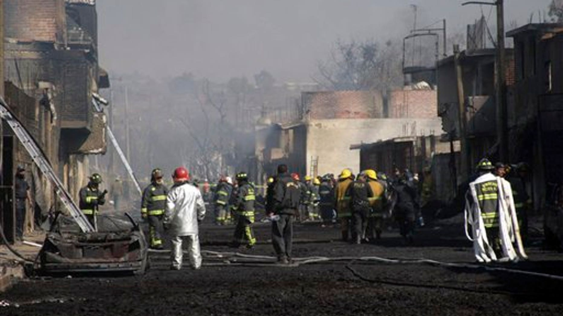 Emergency workers and firefighters work at the scene after a pipeline explosion in San Martin Texmelucan, Mexico, Sunday, Dec. 19, 2010. A pipeline operated by Mexico's state-owned oil company Petroleos Mexicanos, or PEMEX, exploded when thieves were attempting to steal either gas or oil, killing at least 27 people, authorities said. (AP Photo)