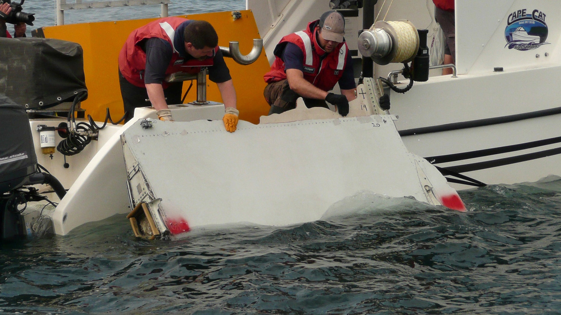 A Boeing 777 flaperon cut down to match the one from flight MH370 found on Reunion island off the coast of Africa in 2015, is lowered into water to discover its drift characteristics by Commonwealth Scientific and Industrial Research Organisation researchers in Tasmania, Australia, in this handout image taken March 23, 2017.