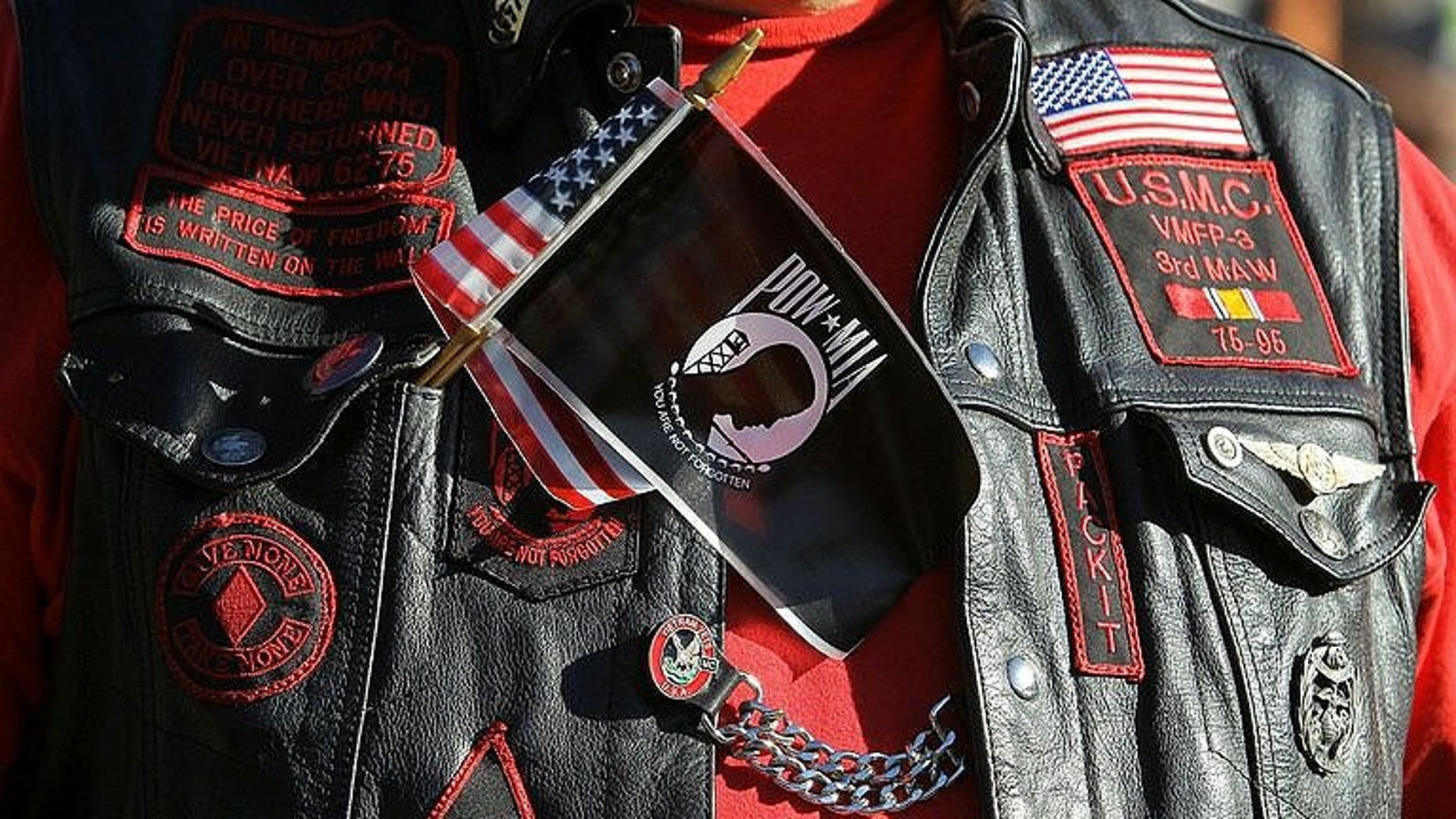 A veteran wears a US and POW-MIA flag together on his vest
