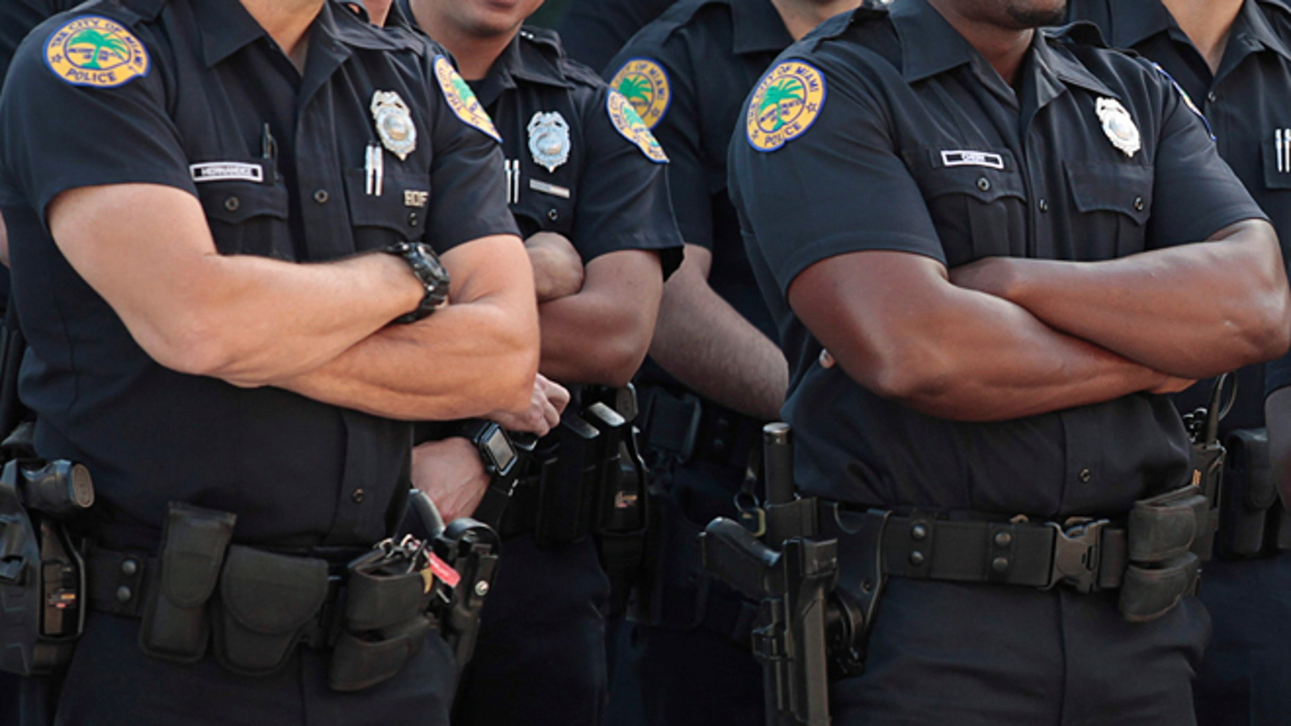 Miami police officers receive instructions from a commanding officer.