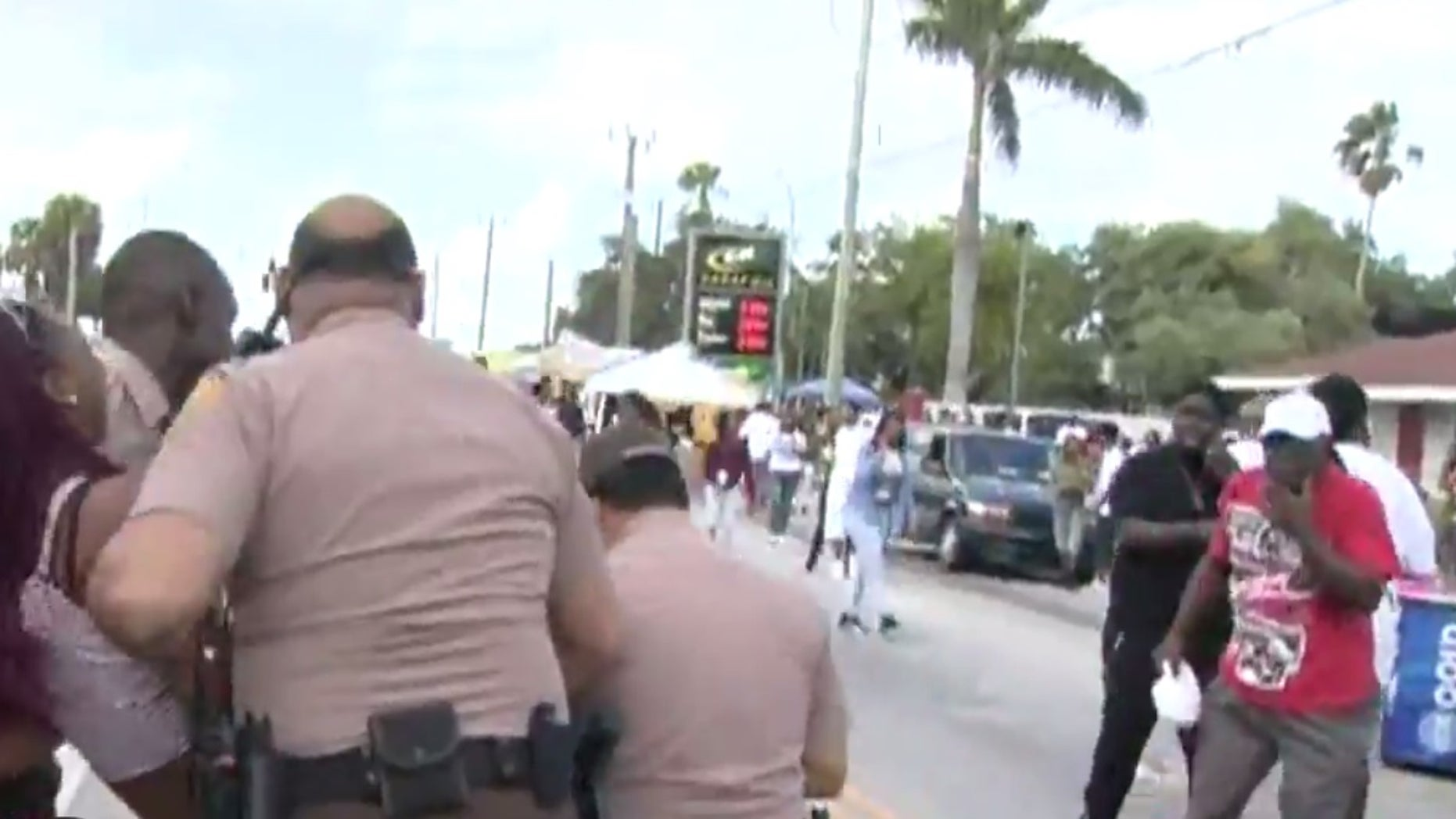 Police carrying away a woman who appeared to be hurt.
