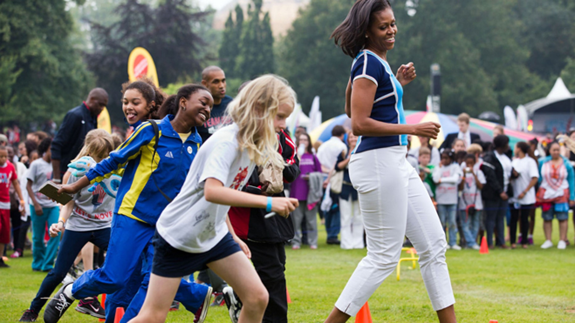 First lady Michelle Obama runs at an activity station during a ìLetís Move! London event at Winfield House in London.