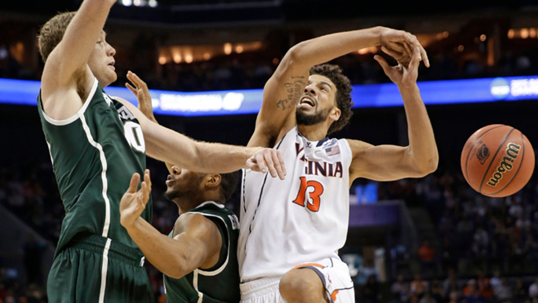 March 22, 2015: Michigan State's Matt Costello, left, knocks the ball from Virginia's Anthony Gill, right, during the second half of an NCAA tournament college basketball game in the Round of 32 in Charlotte, N.C.
