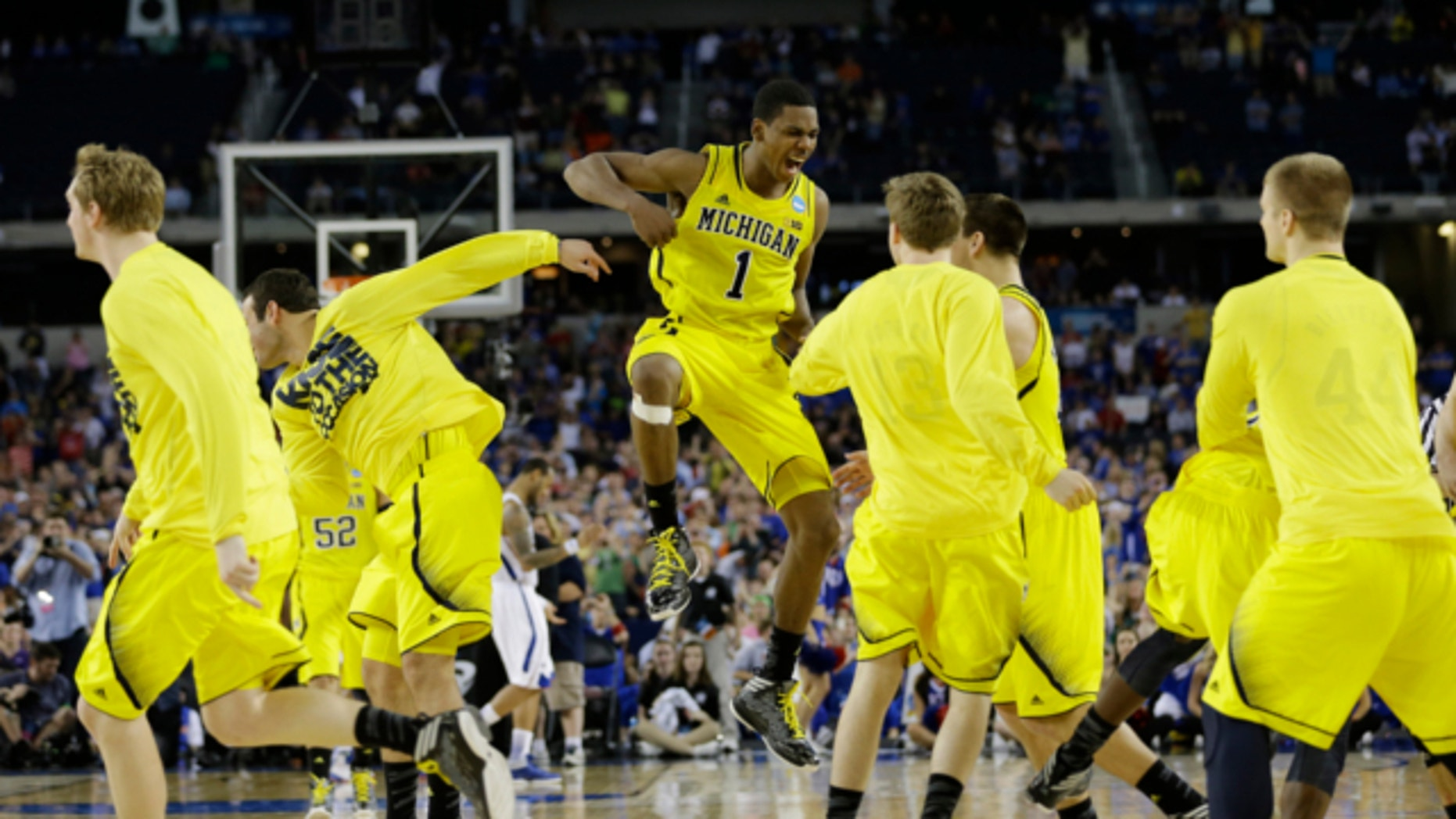 April 6, 2013: Michigan players including Time Hardaway Jr., right, and Nik Stauskas (11) celebrate after defeating Syracuse in their NCAA Final Four tournament college basketball semifinal game in Atlanta. Michigan won 61-56.