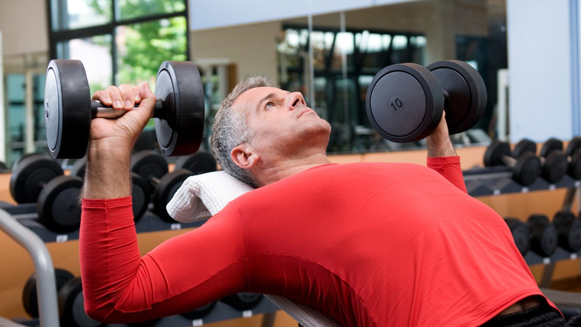 Mature man lifting dumbells at fitness gym
