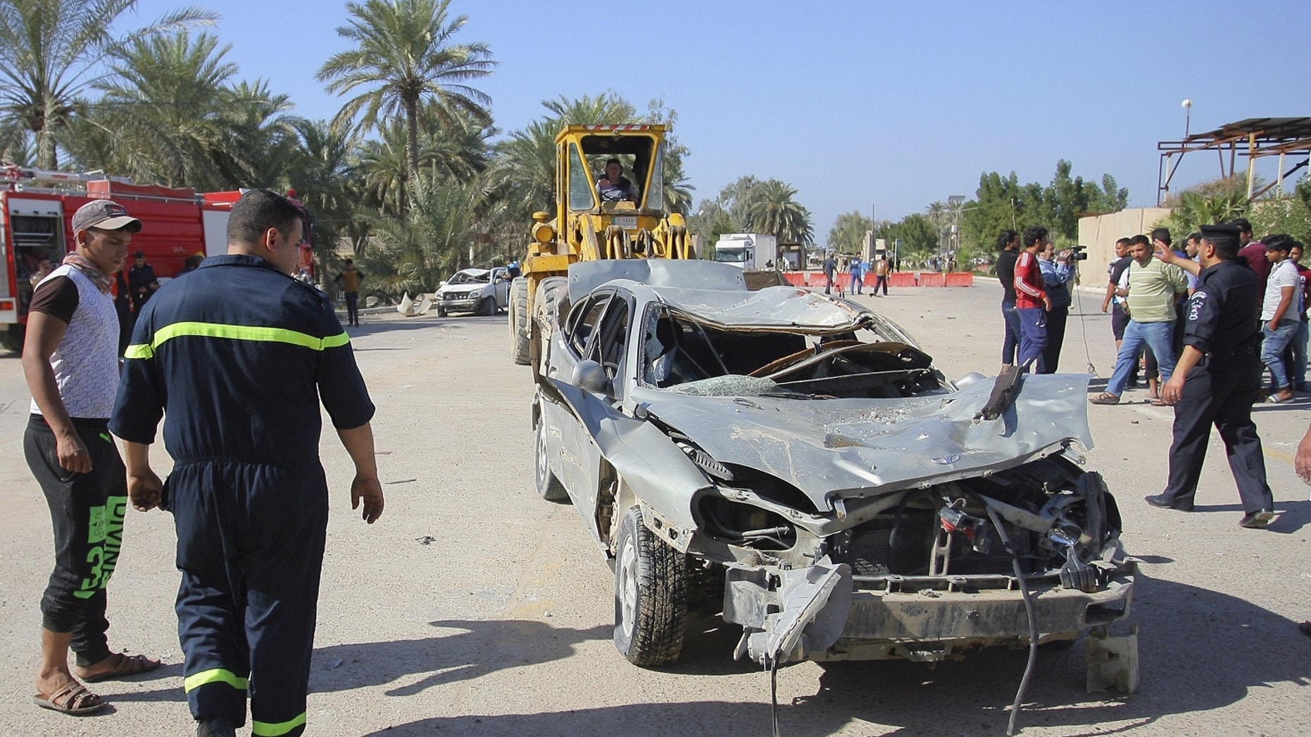 Civilians and security forces gather as municipality workers remove destroyed vehicles at the scene of a suicide bomb attack.