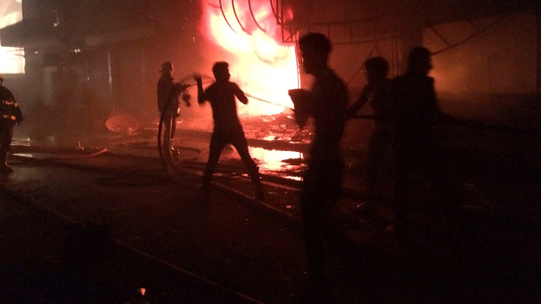 July 3, 2016: Iraqi firefighters extinguish a fire as civilians gather after a car bomb at a commercial area in the Karada neighborhood of Baghdad