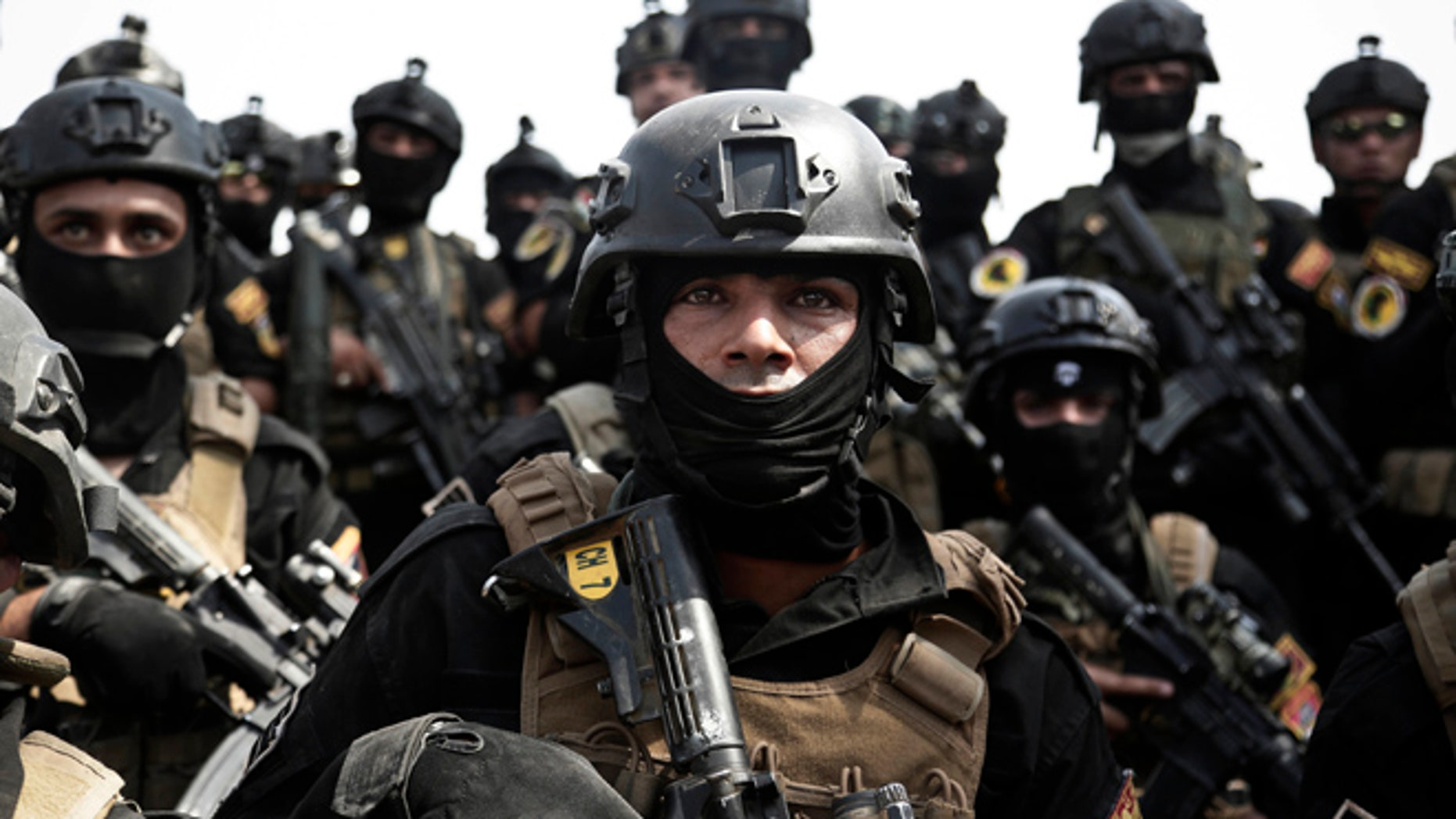 In this Saturday, Aug. 13, 2016 photo, a soldier from the 1st Battalion of the Iraqi Special Operations Forces listens to an address by his commander after a training exercise to prepare for the operation to re-take Mosul from Islamic State militants, in Baghdad, Iraq.