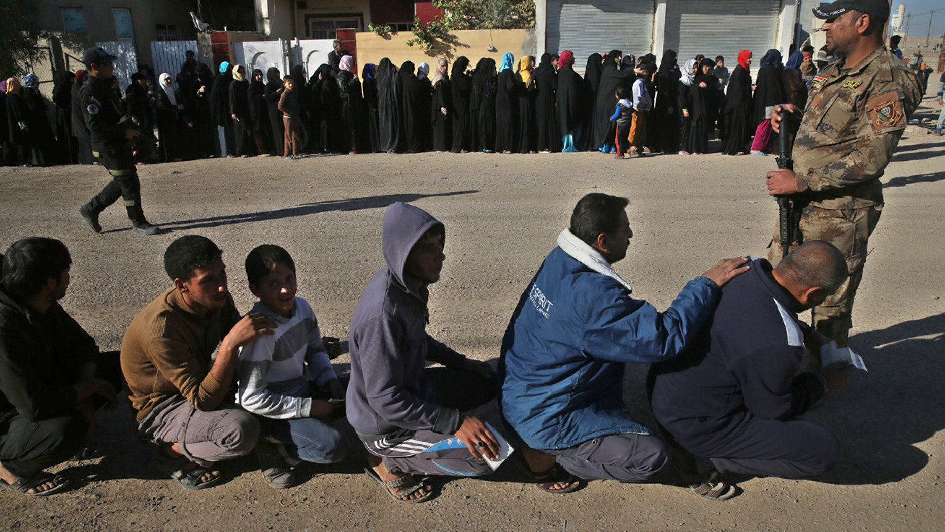 Iraqi citizens que to receive food supplies, at al-Arbajiyeh neighborhood, in Mosul, Iraq, Saturday, Nov. 19, 2016.