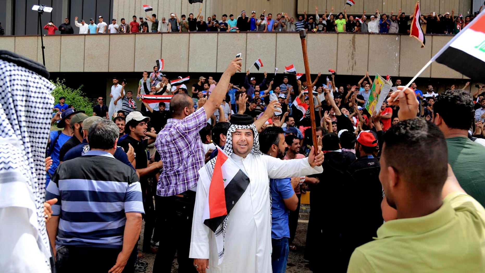 Supporters of Shiite cleric Muqtada al-Sadr chant slogans calling for governmental reforms as they wave national flags before ending their sit-in inside Baghdad's highly fortified Green Zone Sunday.